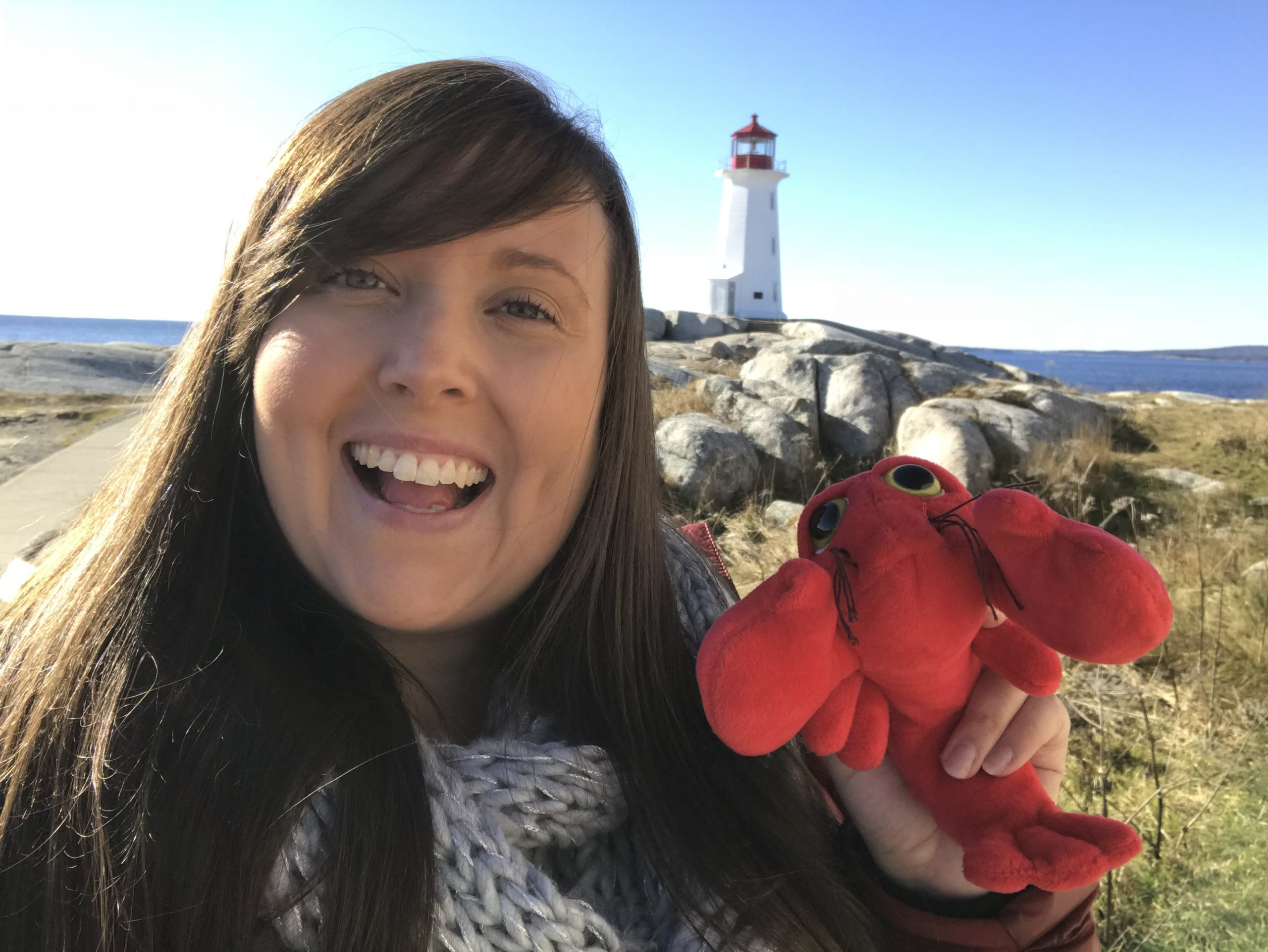 Cailin with a toy lobster at the Peggy's Cove Lighthouse