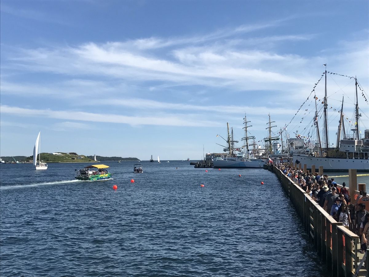 A bustly halifax waterfront boardwalk full of boats and people on a sunny day