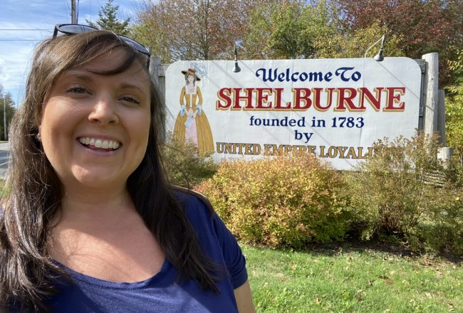 Cailin ONeil with the welcome to shelburne sign WHAT TO SEE, DO AND EAT IN SHELBURNE COUNTY, NOVA SCOTIA